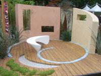 Freiraumplanung mit Kunstobjekt als Sitzgelegenheit und kombinierten Holz- und Steinflächen.